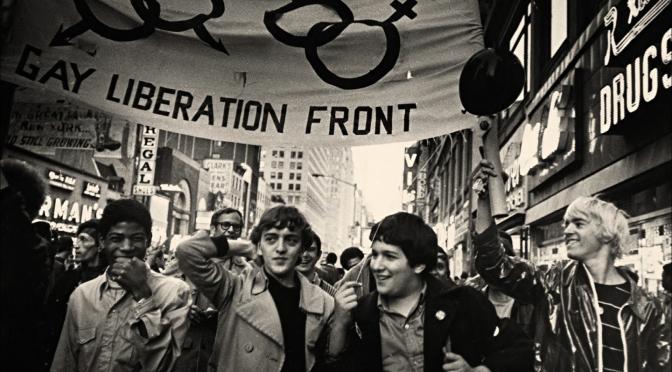 "Manifestación en Nueva YOrk, jóvenes LGTBI+ con pancarta en alto que reza ""Gay Liberation Front"" (Frente de liberación gay)"