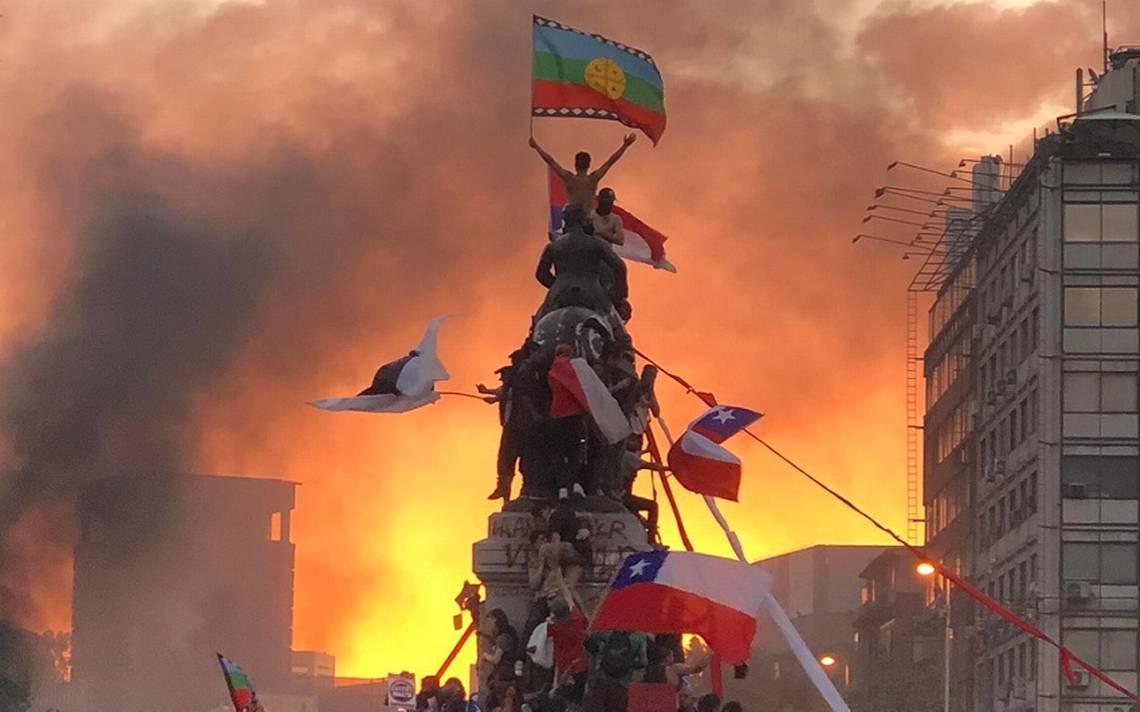 chile manifestante flameando la bandera mapuche en la cima de una estatua militar en Santiago